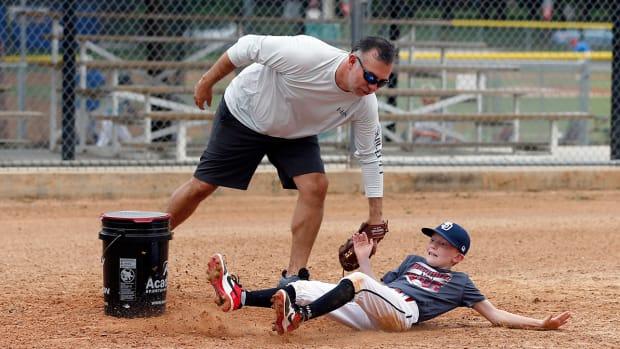 Jun 1, 2020; Alamo Heights, Texas, USA;  Coach Ben Ben Vaello tags out August Berchelman on a drill for the Alamo Heights Little Legue AA team.