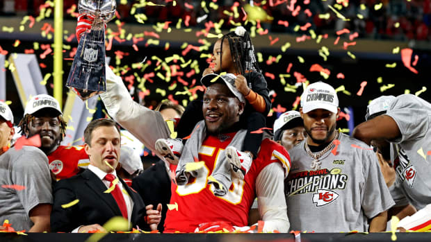 Kansas City Chiefs defensive end Frank Clark (55) celebrates with the Vince Lombardi Trophy after beating the San Francisco 49ers in Super Bowl LIV at Hard Rock Stadium.