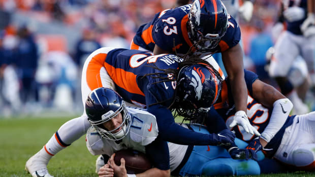 Tennessee Titans quarterback Ryan Tannehill (17) is tackled by Denver Broncos linebacker Alexander Johnson (45) and cornerback Chris Harris Jr. (25) and defensive end Dre'Mont Jones (93) in the fourth quarter at Empower Field at Mile High.