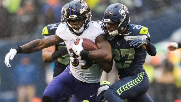 Baltimore Ravens running back Gus Edwards (35) carries the ball while Seattle Seahawks defensive back Marquise Blair (27) tries to tackle during the second half at CenturyLink Field. Baltimore defeated Seattle 30-16.