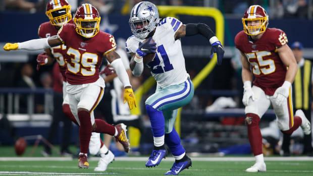 Dallas Cowboys running back Ezekiel Elliott (21) runs against Washington in Dec. 2019. Elliott tested positive for COVID-19 on June 15.