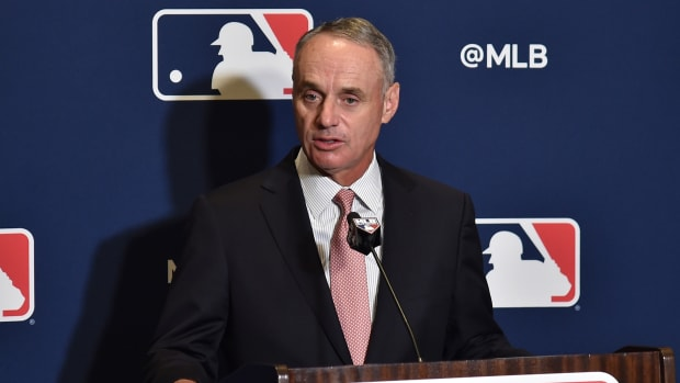 Rob Manfred speaks into a microphone