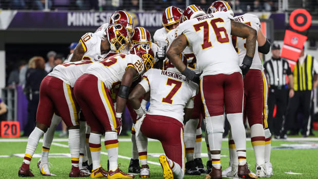 Dwayne Haskins leads a Washington NFL team huddle during a game against the Vikings