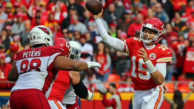 Kansas City Chiefs quarterback Patrick Mahomes (15) throws a pass as Arizona Cardinals defensive tackle Corey Peters (98) defends in the first half at Arrowhead Stadium.