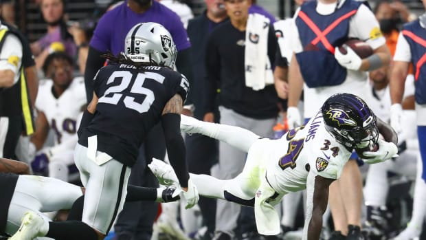 Sep 13, 2021; Paradise, Nevada, USA; Baltimore Ravens running back Ty'Son Williams (34) moves the ball against Las Vegas Raiders safety Trevon Moehrig (25) during the first half at Allegiant Stadium. Mandatory Credit: Mark J. Rebilas-USA TODAY Sports