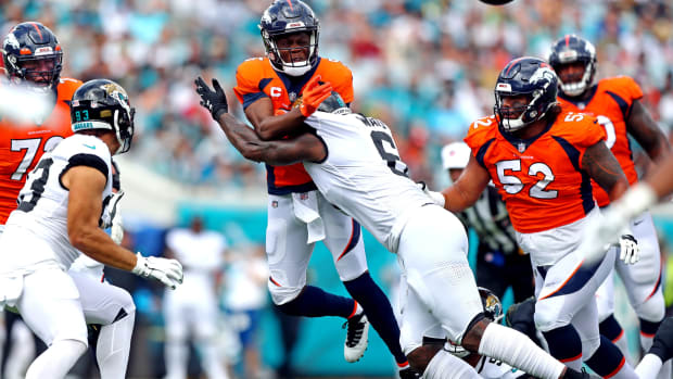 Denver Broncos quarterback Teddy Bridgewater (5) throws a pass while being hit by Jacksonville Jaguars defensive end jihad Ward (6) during the first quarter at TIAA Bank Field.