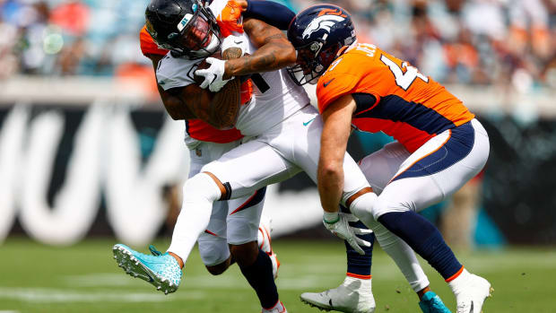 Jacksonville Jaguars wide receiver Marvin Jones (11) is tackled by Denver Broncos cornerback Pat Surtain II (2) and inside linebacker Josey Jewell (47) in the first quarter at TIAA Bank Field.