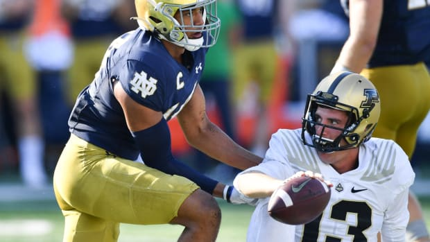 Sep 18, 2021; South Bend, Indiana, USA; Purdue Boilermakers quarterback Jack Plummer (13) is helped up after being tackled by Notre Dame Fighting Irish safety Kyle Hamilton (14) in the third quarter at Notre Dame Stadium. Mandatory Credit: Matt Cashore-USA TODAY Sports