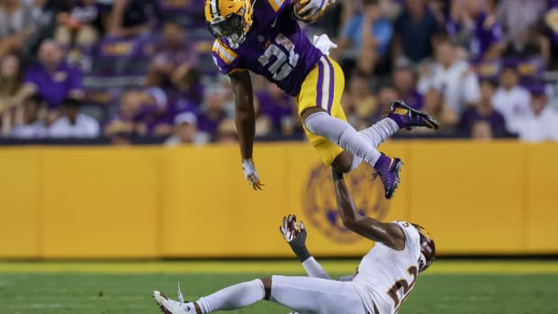 Sep 18, 2021; Baton Rouge, Louisiana, USA; LSU Tigers running back Corey Kiner (21) is tackled as he leaps over Central Michigan Chippewas defensive back Dishon McNary (25) during the first half at Tiger Stadium. Mandatory Credit: Stephen Lew-USA TODAY Sports