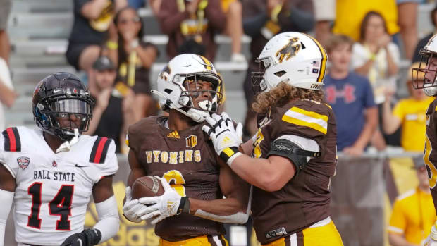 Sep 18, 2021; Laramie, Wyoming, USA; Wyoming Cowboys running back Xazavian Valladay (6) scores a touchdown against the Ball State Cardinals during the fourth quarter at Jonah Field at War Memorial Stadium. Mandatory Credit: Troy Babbitt-USA TODAY Sports