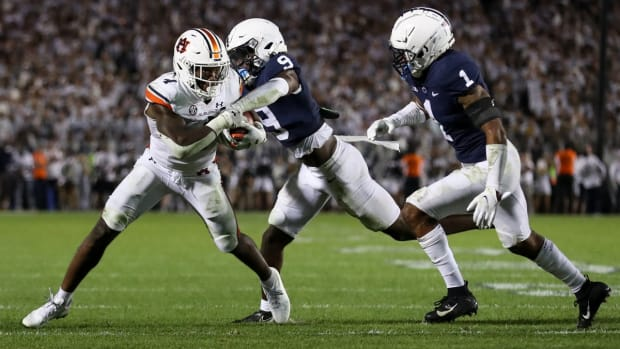 Sep 18, 2021; University Park, Pennsylvania, USA; Auburn Tigers running back Tank Bigsby (4) runs with the ball as Penn State Nittany Lions cornerback Joey Porter Jr. (9) tries the rip the ball away during the fourth quarter at Beaver Stadium. Penn State defeated Auburn 28-20. Mandatory Credit: Matthew OHaren-USA TODAY Sports
