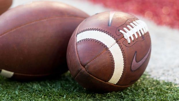 NCAA footballs sit on the ground