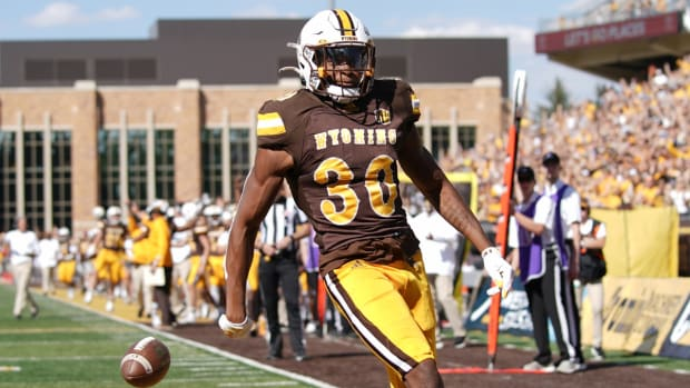 Sep 18, 2021; Laramie, Wyoming, USA; Wyoming Cowboys running back Dawaiian McNeely (30) scores a touchdown against the Ball State Cardinals during the second quarter at Jonah Field at War Memorial Stadium. Mandatory Credit: Troy Babbitt-USA TODAY Sports