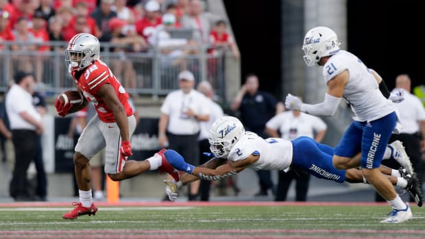Ohio State Buckeyes running back TreVeyon Henderson (32) evades Tulsa Golden Hurricane cornerback Travon Fuller (2) and Tulsa Golden Hurricane safety Bryson Powers (21) during the second half of Saturday's NCAA Division I football game on September 18, 2021. Ohio State won the game 41-20.  Osu21tlsa Bjp 1072