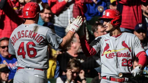 Nolan Arenado greets Cardinals teammate Paul Goldschmidt after the first baseman hit a three-run home run vs. Milwaukee.