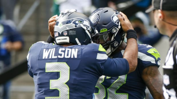 Sep 19, 2021; Seattle, Washington, USA; Seattle Seahawks running back Chris Carson (32) celebrates with quarterback Russell Wilson (3) after rushing for a touchdown against the Tennessee Titans during the second quarter at Lumen Field. Mandatory Credit: Joe Nicholson-USA TODAY Sports