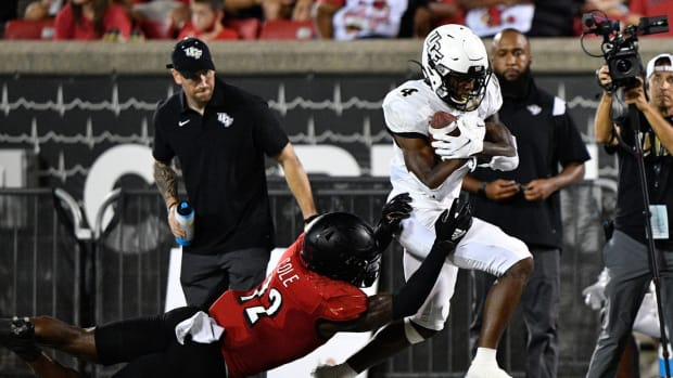 Sep 17, 2021; Louisville, Kentucky, USA; UCF Knights wide receiver Ryan O'Keefe (4) out runs the tackle of Louisville Cardinals defensive back Qwynnterrio Cole (12) during the second half at Cardinal Stadium. Louisville defeated Central Florida 42-35. Mandatory Credit: Jamie Rhodes-USA TODAY Sports