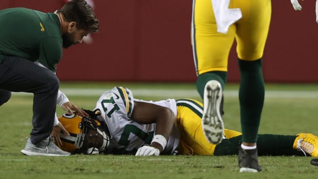 Davante Adams lays on the turf after being hit by 49ers safety Jimmie Ward.