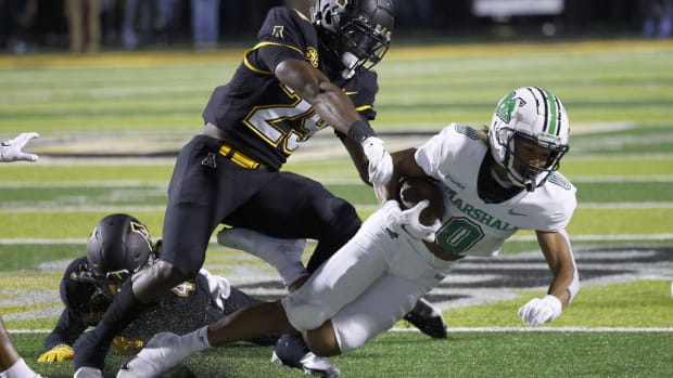 Sep 23, 2021; Boone, North Carolina, USA; Appalachian State Mountaineers defensive back Nick Ross (4) and linebacker Brendan Harrington (29) combine to bring down Marshall Thundering Herd wide receiver Shadeed Ahmed (0) during the second half at Kidd Brewer Stadium. Mandatory Credit: Reinhold Matay-USA TODAY Sports
