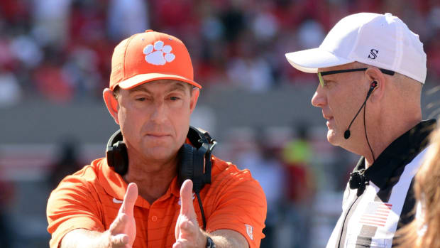 Sep 25, 2021; Raleigh, North Carolina, USA; Clemson Tigers head coach Dabo Swinney (left) talks to an official during the first half against the North Carolina State Wolfpack at Carter-Finley Stadium. Mandatory Credit: Rob Kinnan-USA TODAY Sports
