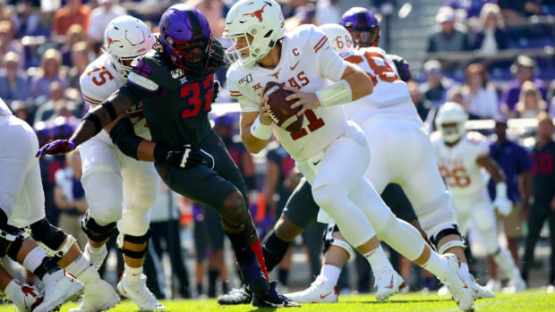Oct 26, 2019; Fort Worth, TX, USA; Texas Longhorns quarterback Sam Ehlinger (11) looks to throws as TCU Horned Frogs defensive end Ochaun Mathis (32) chases during the first quarter at Amon G. Carter Stadium.