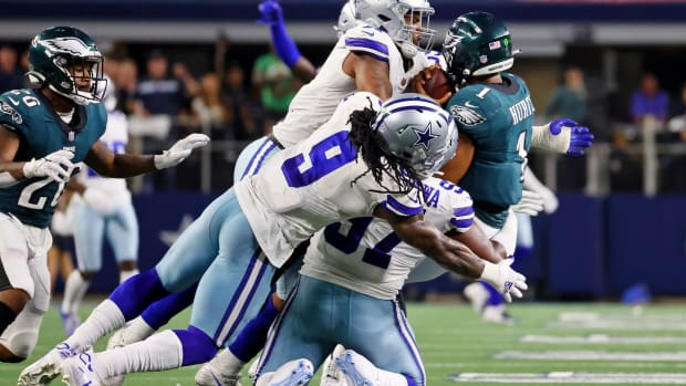 Sep 27, 2021; Arlington, Texas, USA; Philadelphia Eagles quarterback Jalen Hurts (1) is tackled by Dallas Cowboys linebacker Micah Parsons (top) and middle linebacker Jaylon Smith (left) and defensive tackle Osa Odighizuwa (bottom) during the fourth quarter at AT&T Stadium.