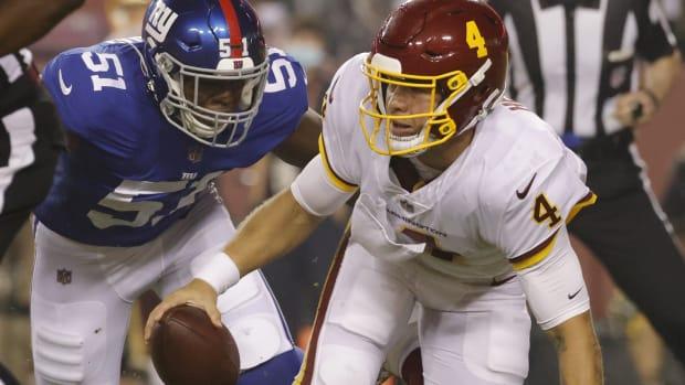 Sep 16, 2021; Landover, Maryland, USA; Washington Football Team quarterback Taylor Heinicke (4) is sacked by New York Giants linebacker Azeez Ojulari (51) in the first quarter at FedExField.