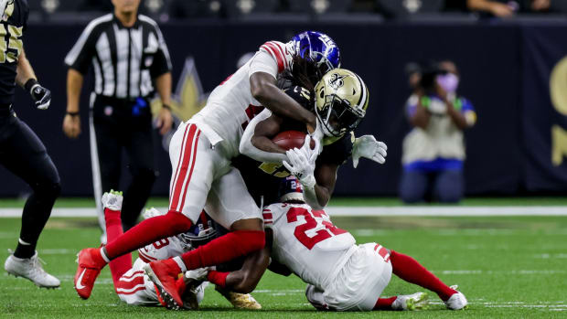 Oct 3, 2021; New Orleans, Louisiana, USA; New Orleans Saints running back Alvin Kamara (41) is tackled by New York Giants cornerback Logan Ryan (23) during the first half at Caesars Superdome.