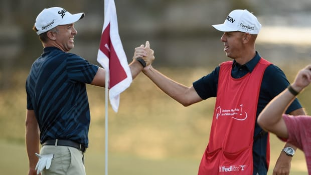 Martin Laird celebrates the 2020 Shriners Open title with his caddie.