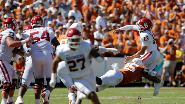 Oklahoma's Caleb Williams (13) is hit by Texas's Alfred Collins (95) as he throws a pass during the Red River Showdown college football game between the University of Oklahoma Sooners (OU) and the University of Texas (UT) Longhorns at the Cotton Bowl in Dallas, Saturday, Oct. 9, 2021. Oklahoma won 55-48. Ou Vs Texas