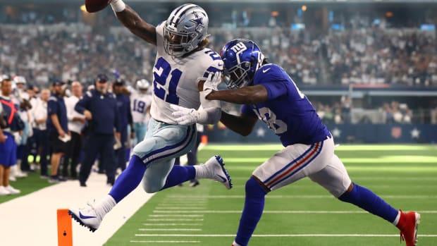 Oct 10, 2021; Arlington, Texas, USA; Dallas Cowboys running back Ezekiel Elliott (21) scores a third quarter touchdown against New York Giants linebacker Tae Crowder (48) at AT&T Stadium.