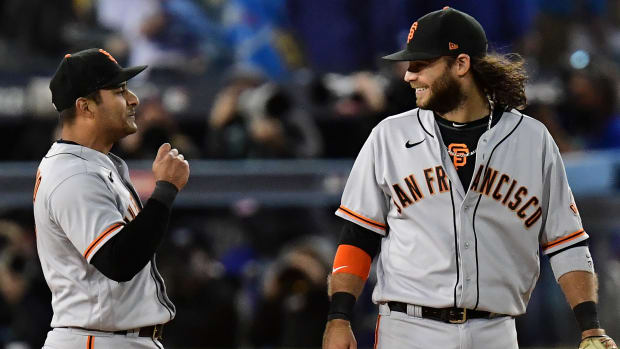 San Francisco Giants shortstop Brandon Crawford (35) and second baseman Donovan Solano (7) celebrate after defeating the Los Angeles Dodgers in game three of the 2021 NLDS at Dodger Stadium.