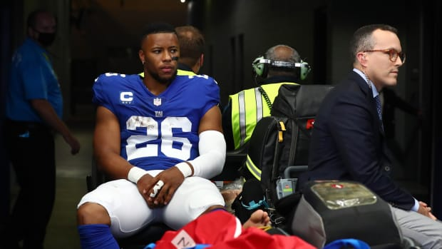 Oct 10, 2021; Arlington, Texas, USA; New York Giants running back Saquon Barkley (26) heads to the locker room on a medical cart in the first half during the game against the Dallas Cowboys at AT&T Stadium.