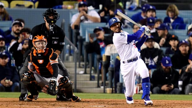 Oct 12, 2021; Los Angeles, California, USA; Los Angeles Dodgers right fielder Mookie Betts (50) hits a two-run home run during the fourth inning against the San Francisco Giants in Game 4 of the 2021 NLDS at Dodger Stadium.