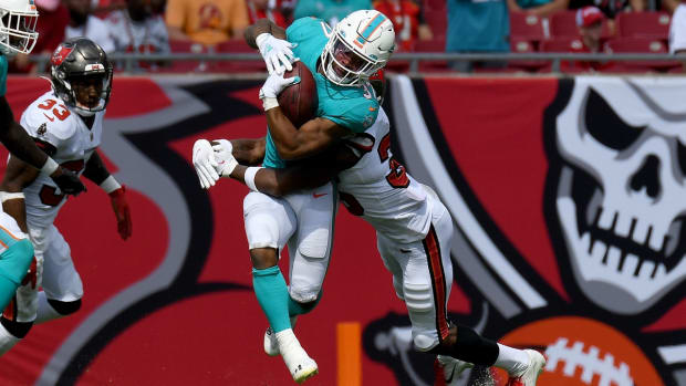 Oct 10, 2021; Tampa, Florida, USA; Miami Dolphins running back Myles Gaskin (37) attempts to get past Tampa Bay Buccaneers defensive back Jamel Dean (35) in the second half at Raymond James Stadium. Mandatory Credit: Jonathan Dyer-USA TODAY Sports