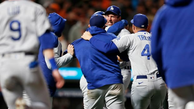 Oct 14, 2021; San Francisco, California, USA; Los Angeles Dodgers pitcher Max Scherzer (facing camera) is mobbed by teammates after defeating the San Francisco Giants in game five of the 2021 NLDS at Oracle Park.