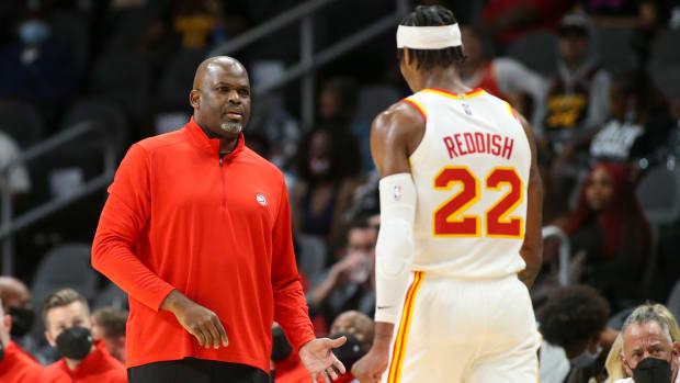 Atlanta Hawks head coach Nate McMillan talks to forward Cam Reddish (22) against the Miami Heat in the first half at State Farm Arena.