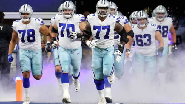 ARLINGTON, TEXAS - OCTOBER 03: Terence Steele #78, Zack Martin #70, and Tyron Smith #77 of the Dallas Cowboys lead the team on to the field before the game against the Carolina Panthers at AT&T Stadium on October 03, 2021 in Arlington, Texas. (Photo by Richard Rodriguez/Getty Images)