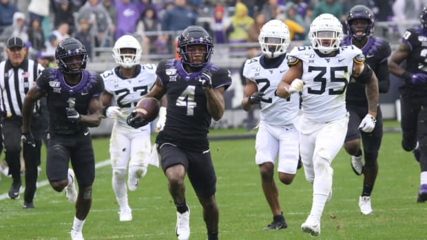 TCU wide receiver Taye Barber runs away from West Virginia defenders in the 2019 game in Fort Worth.