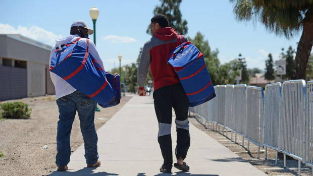 Mar 15, 2020; Surprise, Arizona, USA; Texas Rangers prospects Tyreque Reed (white shirt) and Bubba Thompson (red/gray shirt) leave Surprise Stadium following the cancellation of spring training games due to concerns over the COVID-19 coronavirus. Mandatory Credit: Joe Camporeale-USA TODAY Sports