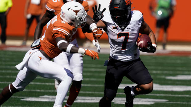 Oct 16, 2021; Austin, Texas, USA; Oklahoma State Cowboys running back Jaylen Warren (7) tries to avoid a tackle by Texas Longhorns defensive back D'Shawn Jamison (5) while running for yardage in the second half of the game at Darrell K Royal-Texas Memorial Stadium. Mandatory Credit: Scott Wachter-USA TODAY Sports