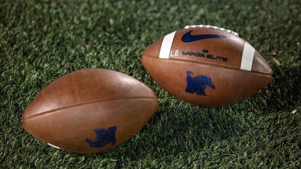 Memphis' AAC footballs on a field.