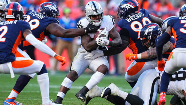 Las Vegas Raiders running back Josh Jacobs (28) carries past Denver Broncos defensive tackle Shamar Stephen (99) and defensive end DeShawn Williams (90) in the second half at Empower Field at Mile High.