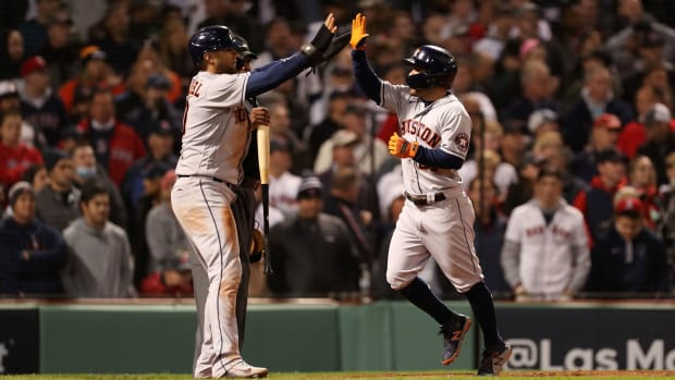 Houston Astros second baseman Jose Altuve (27) celebrates with first baseman Yuli Gurriel (10) after scoring during the ninth inning of game four of the 2021 ALCS at Fenway Park.