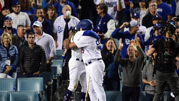Oct 21, 2021; Los Angeles, California, USA; Los Angeles Dodgers left fielder AJ Pollock (11) embraces first baseman Albert Pujols (55) after hitting a three run home run in the eighth inning against the Atlanta Braves during game five of the 2021 NLCS at Dodger Stadium.