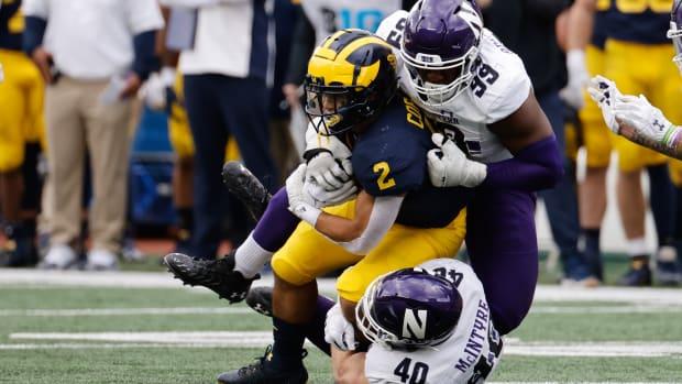 Michigan Wolverines running back Blake Corum (2) is tackled by Northwestern Wildcats linebacker Peter McIntyre (40) and defensive lineman Adetomiwa Adebawore (99) in the first half at Michigan Stadium. Rick Osentoski-USA TODAY Sports