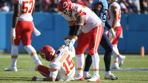 Oct 24, 2021; Nashville, Tennessee, USA; Kansas City Chiefs quarterback Patrick Mahomes (15) is helped up by Kansas City Chiefs guard Mike Remmers (75) after being hit during the second half against the Tennessee Titans at Nissan Stadium. Mandatory Credit: Christopher Hanewinckel-USA TODAY Sports