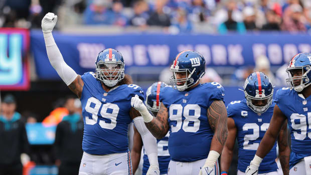 Oct 24, 2021; East Rutherford, New Jersey, USA; New York Giants defensive end Leonard Williams (99) gestures in front of nose tackle Austin Johnson (98) against the Carolina Panthers during the second half at MetLife Stadium.