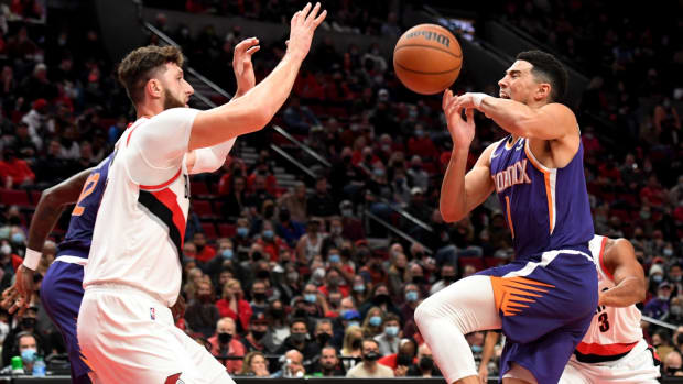 Oct 23, 2021; Portland, Oregon, USA; Phoenix Suns guard Devin Booker (1) loses control of the ball as he drives to the basket on Portland Trail Blazers center Jusuf Nurkic (27) during the first quarter of the game at Moda Center. Mandatory Credit: Steve Dykes-USA TODAY Sports
