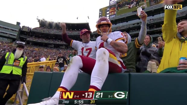 Taylor Heinicke sits in the stands after doing the Lambeau Leap